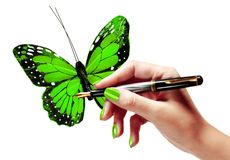 Woman's hand is painting a vivid green butterfly Stock Photo