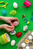 Woman`s hand paints eggs. Top view woman`s hand paints eggs, on green background stencils, paints. ribbons, watering can. preparation for the holiday royalty free stock photography