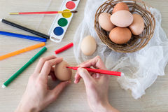 Woman`s hand paints hen`s egg food marker for Easter. Royalty Free Stock Photography