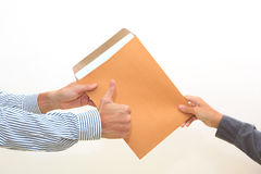 Woman's hand passes envelope to male hand on white Royalty Free Stock Images