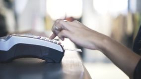 Woman s hand paying with credit card in store. Close up of woman s hand paying with a credit card using a portable machine in store. Locked down real time close stock footage