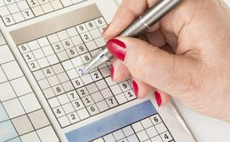 Woman`s hand with a pen is filling out sudoku royalty free stock photography