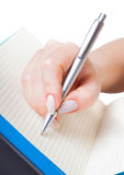Woman's hand with a pen writing Stock Images