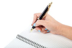 Woman's hand with a pen writing in a notebook. Stock Photos