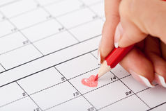 Woman`s hand with pencil and calendar. Woman`s hand with pencil try to drawing heart shape in calendar in Valentines day Royalty Free Stock Photos