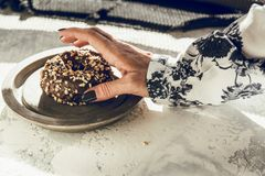 Woman`s hand picking a chocolate donut Stock Photo
