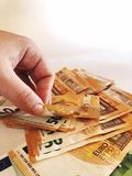 Hand and pile of €50 banknotes stock photography
