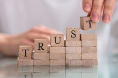 Woman`s Hand Placing Last Alphabet Of Word Trust