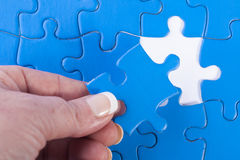Woman's hand placing missing piece in Jigsaw puzzle  signifying Royalty Free Stock Image