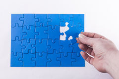 Woman's hand placing missing piece in Jigsaw puzzle  signifying Stock Photos