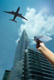 A woman's hand play with a paper airplane. In front of a background of sky and skyscraper Royalty Free Stock Photography
