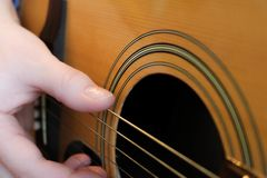 Woman`s hand playing a guitar. Close up of woman`s hand with glittery nail polish playing an acoustic guitar Stock Photo