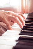 Woman's hand playing piano. Closeup woman's hand playing piano. Favorite classical music. With color filter. Pastel and warm color tone. Vintage and retro color Stock Photography