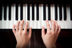 Woman's hand playing piano. Closeup woman's hand playing piano. Favorite classical music. Top view with dark vignette Royalty Free Stock Images