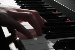 Woman's hand playing the piano stock photos