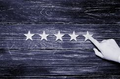 A woman`s hand points to the fifth star. Quality status is five. Stars. A new star, achievement, universal recognition. Wooden stars on a black background royalty free stock image
