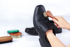 Woman's hand polishing black leather shoes Royalty Free Stock Photos