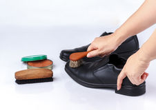 Woman's hand polishing black leather shoes Stock Images