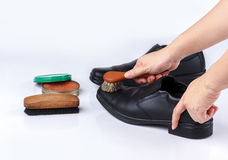 Woman's hand polishing black leather shoes Stock Image
