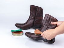 Woman's hand polishing boot with shoe brush Stock Images