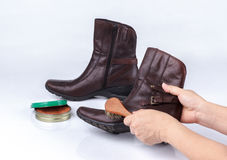 Woman's hand polishing boot with shoe brush Stock Photography