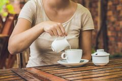 Woman`s hand pouring milk in white cup of coffee in outdoor cafe Royalty Free Stock Images