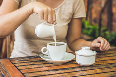 Woman`s hand pouring milk in white cup of coffee in outdoor cafe Royalty Free Stock Photo