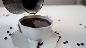 The woman`s hand pours coffee from a Turkish coffee pot into a white cup on a white table. Cinnamon and coffee beans.  stock video footage