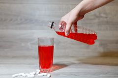 A woman's hand pours a red sports drink or lemonade into a glass Cup from a plastic bottle. Energy drink in glass and plastic bot royalty free stock image