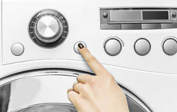 Woman`s hand presses a button on the washing machine. Royalty Free Stock Image