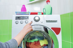 Woman`s hand presses a button on the washing machine. Royalty Free Stock Photo