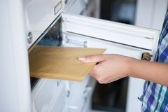 Woman's hand pulling envelop from mailbox Stock Photos