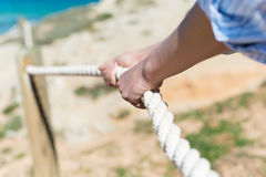 Woman's Hand Pulling Rope Of Railing At Beach. Closeup of woman's hand pulling rope of railing at beach Royalty Free Stock Photography
