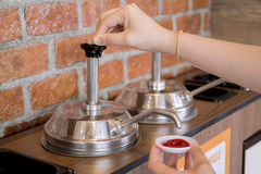 Woman`s hand pumping the ketchup pump. With brick wall pattern background Stock Photo