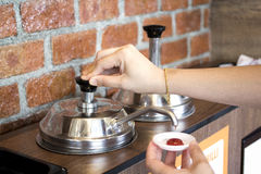 Woman`s hand pumping the ketchup pump. With brick wall pattern background stock photos