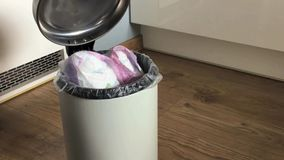 Woman`s hand put used diapers one by one in the garbage can at home. stock video