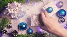 Woman`s hand puts a Christmas wrapped gift on a decorated table with flashing lights and cones top view. 0:11 sec stock video