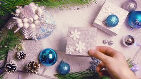Woman`s hand puts a Christmas wrapped gift on a decorated table with flashing lights and cones top view. 0:12 sec stock footage