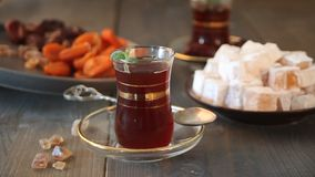 Woman`s hand puts plate with dry fruits sweets on the wooden table with turkish tea in traditional glass cups. Oriental. Woman`s hand puts plate with dry fruits stock video footage