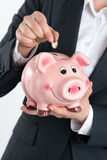 Woman's hand putting coin into piggy bank. Save money or investment concept Stock Photography