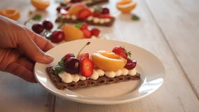 Woman`s hand putting crisp fitness health bread with creme cheese, fruit and berries on the white wooden background. Woman`s hand putting crisp fitness health stock video footage