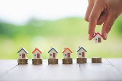 Woman`s hand putting house model on coins stack. Concept for property ladder, planning savings money of coins to buy a home. Concept property mortgage and stock photography