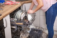 Woman`s hand putting a white plate into the dishwasher a household chore. Loading dishwasher stock photos