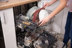 Woman`s hand putting a white plate into the dishwasher a household chore. Loading dishwasher stock photo