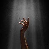 Woman's hand reaches for the light rays Stock Photo