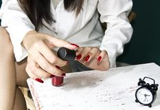 Woman's hand and red lacquer Stock Photography