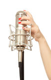 Woman's hand with red nails holding microphone Stock Photos