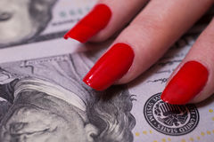 Woman's hand with red nails lying on the money Royalty Free Stock Photography