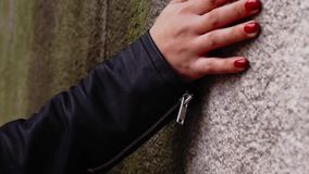 Woman's hand with red nails touching concrete wall stock video