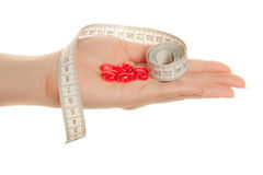 Woman's hand with  red pills and tape measure. Woman's hand holding   red pills and tape measure isolated on white Royalty Free Stock Photo
